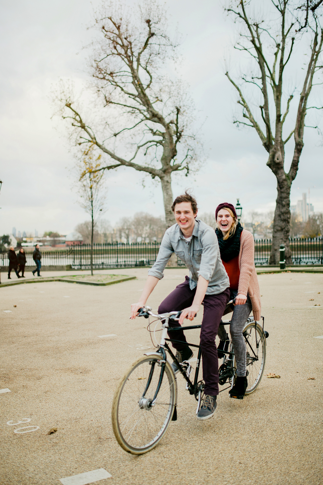 Couple riding on a tandem bike in greenwich park