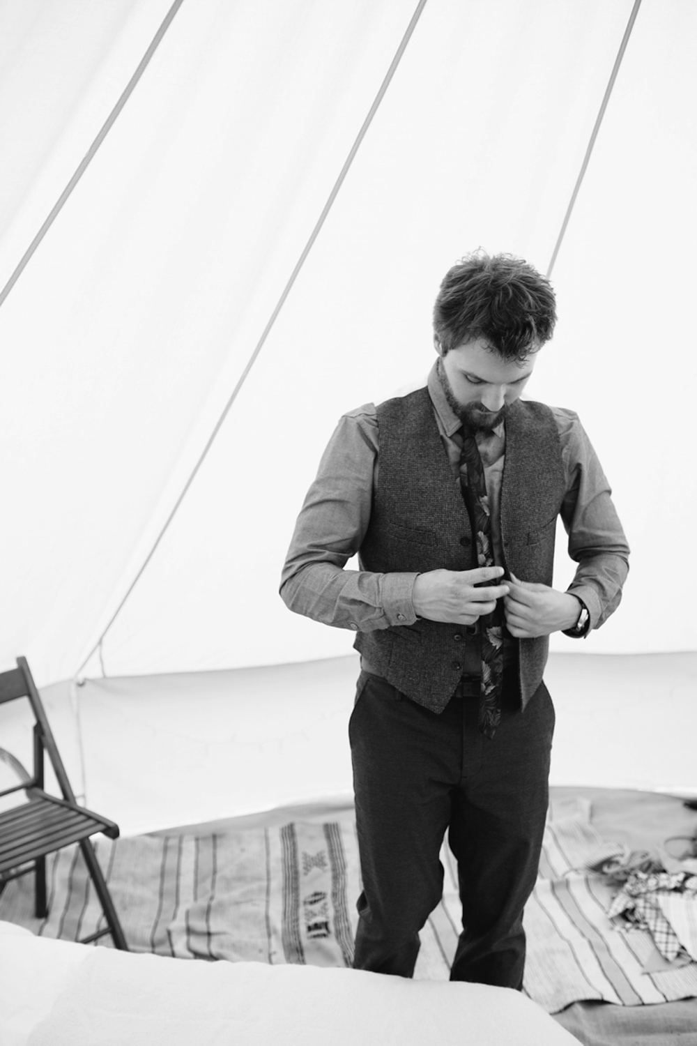 Groom getting dressed in a tent by Hawarden festival wedding photographer