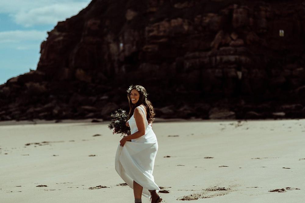 bride walking on the beach towards her groom