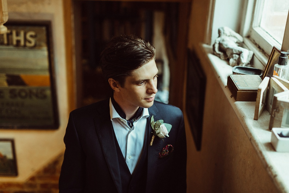 groom's moody portrait by the window on the morning of the wedding