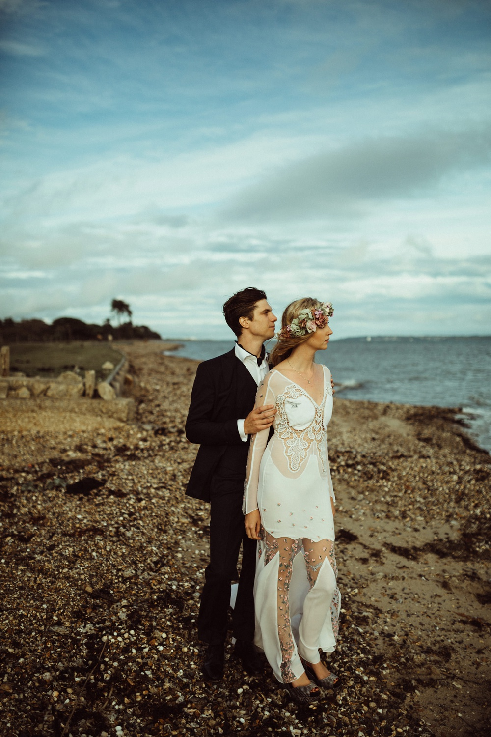 groom holding bride on the sea shore in New Forest, England