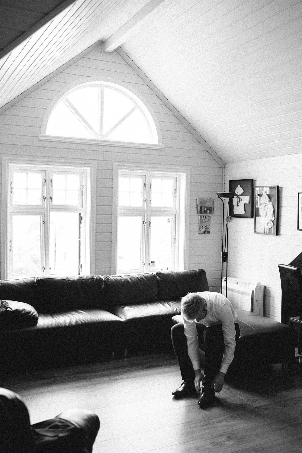 black and white image of groom getting ready for wedding in his home