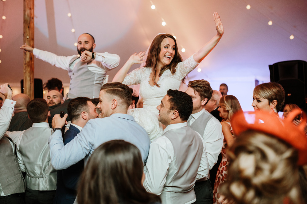 bride and groom lifted in the air during marquee wedding reception
