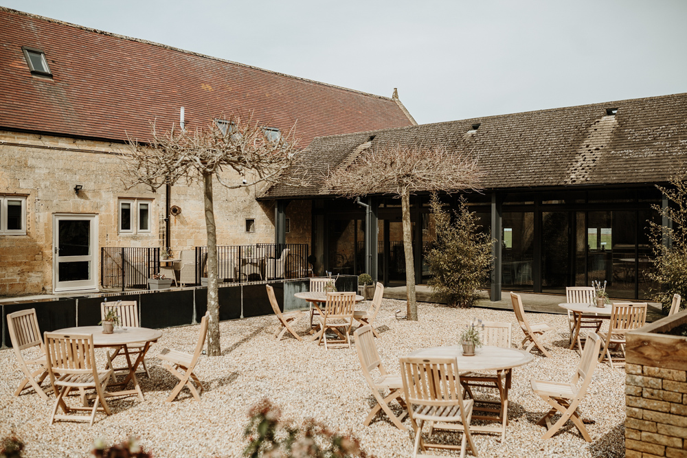 garden area with wooden tables and olive trees at Lapstone Barn wedding venue Cotswolds
