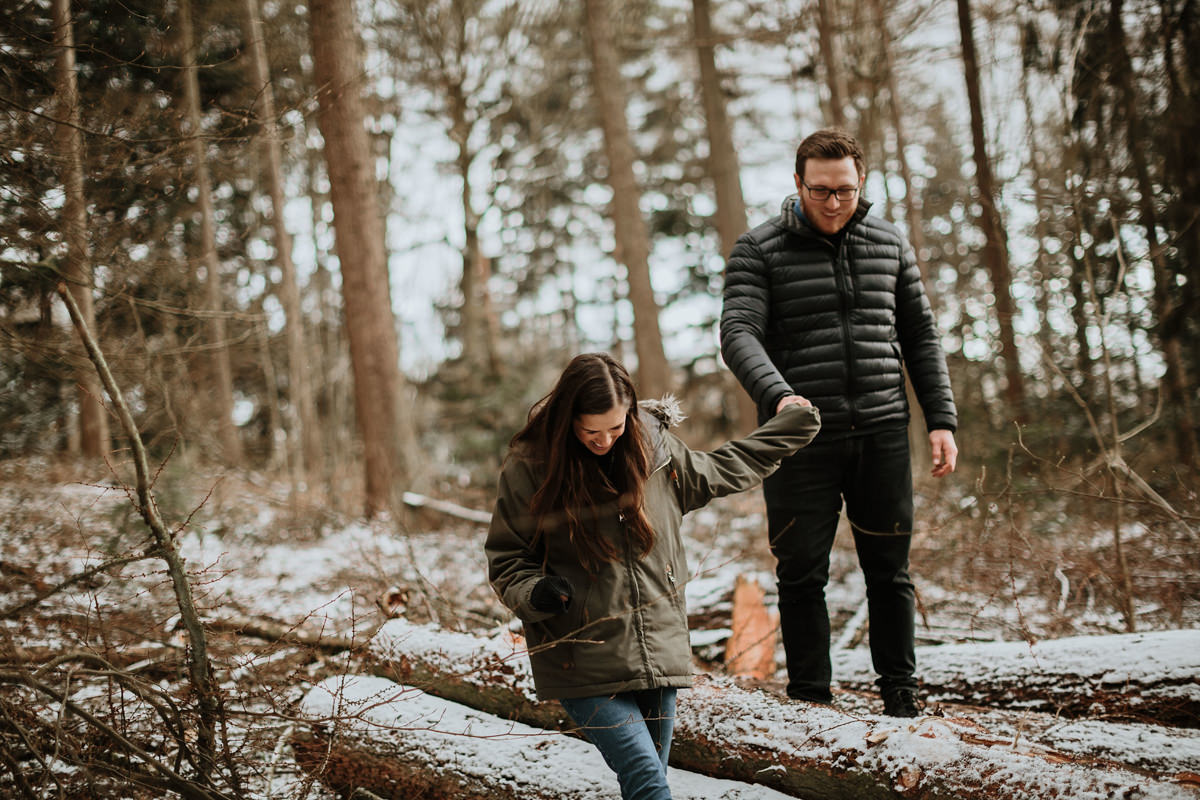 couple walking on fallen logs in Wyre Forest