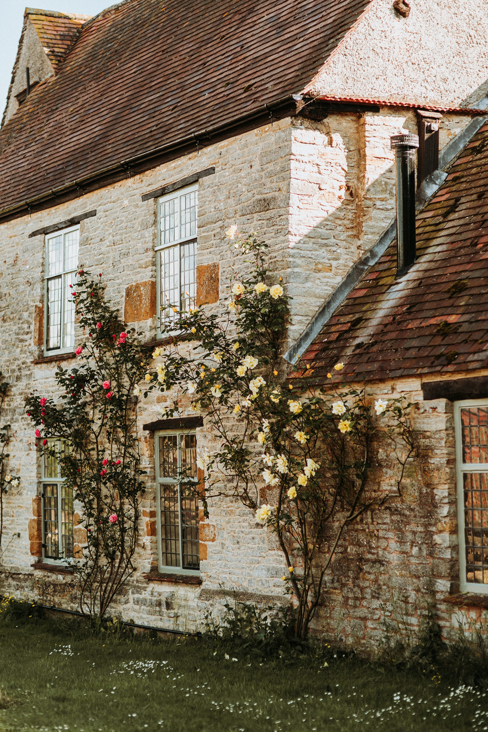stone house with roses by the large windows in the Cotswolds countryside