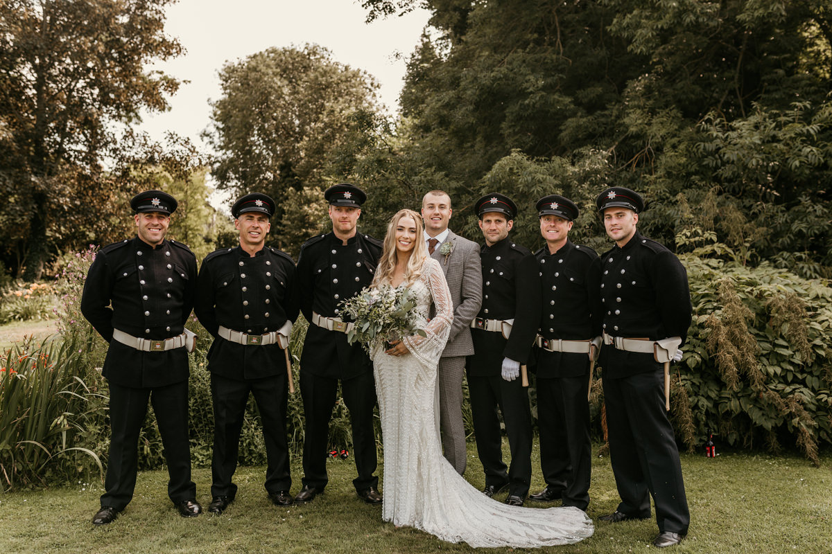 bride and groom with firemen groomsmen at Preston court wedding venue by Canterbury wedding photographers