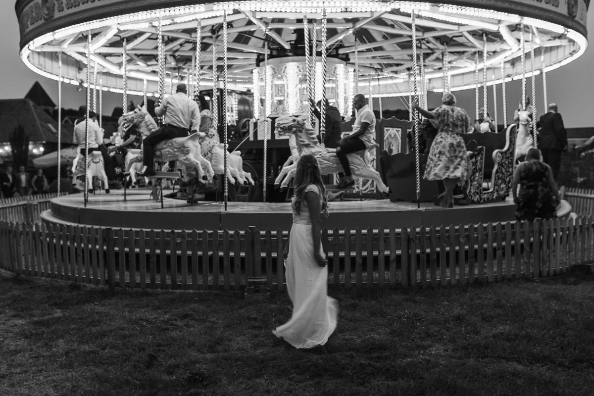 black and white image of bride in front of a carousel spinning at preston court wedding venue by Canterbury wedding photographers