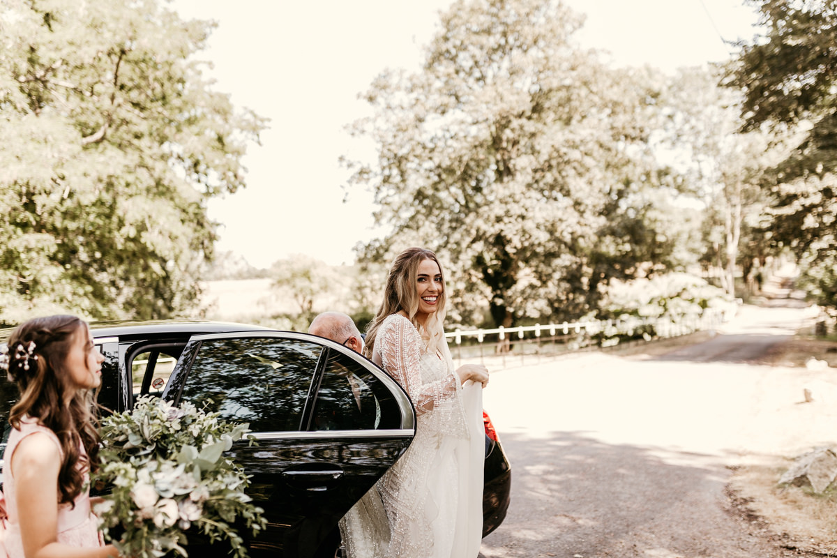 bride wearing a Justin Alexander wedding dress coming out of the car for her church wedding ceremony Canterbury