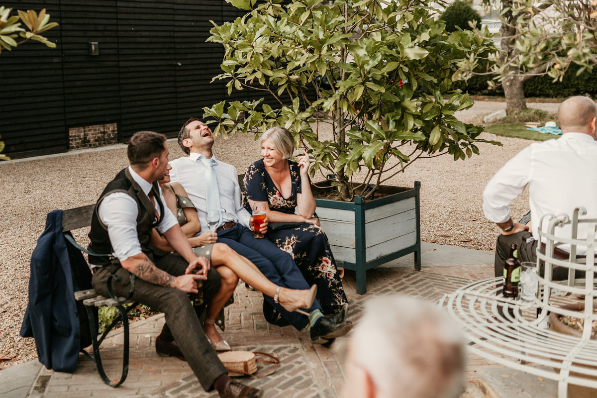 guests laughing during the reception in the gardens of preston court wedding venue by Canterbury wedding photographers