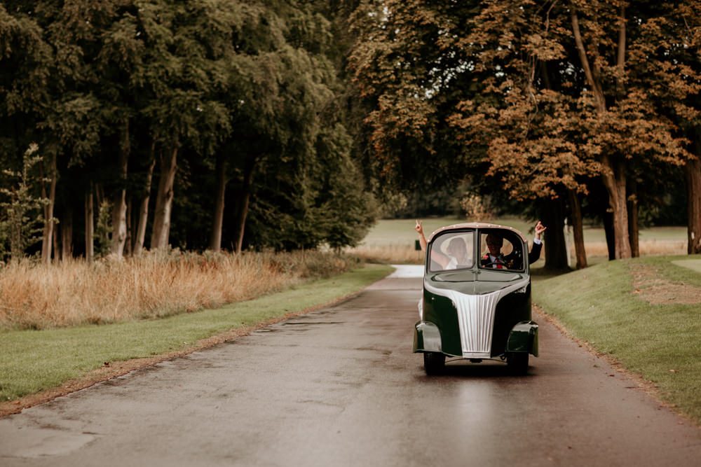 bride and groom in golf car at The Kennels Goodwood wedding venue South England