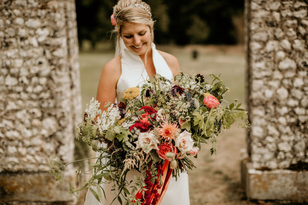 bride wearing a jesus peiro wedding dress with huge boho flowers at The Kennels Goodwood country house wedding venue