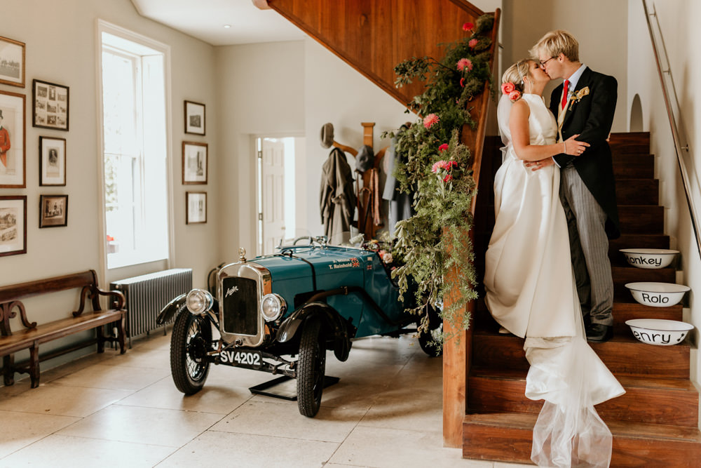 bride and groom inside The Kennels Goodwood country house wedding venue with the Austin vintage car inside the venue