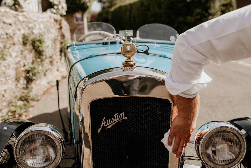 groom polishing an Austin 7 Ulster for his Goodwood wedding