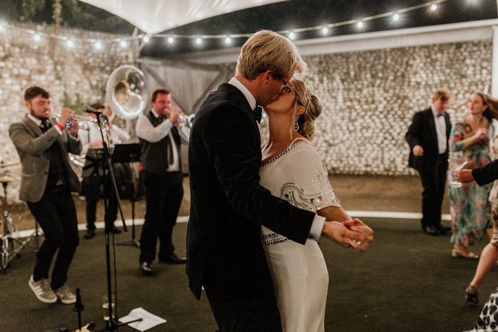 bride and groom kiss at The Kennels Goodwood wedding venue during the reception