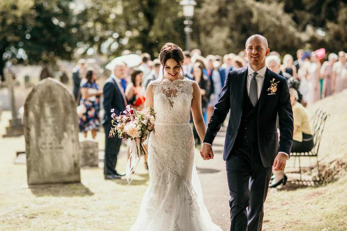 bride and groom holding hands after church ceremony at Merriscourt Barn Wedding venue by Cotswolds wedding photographer