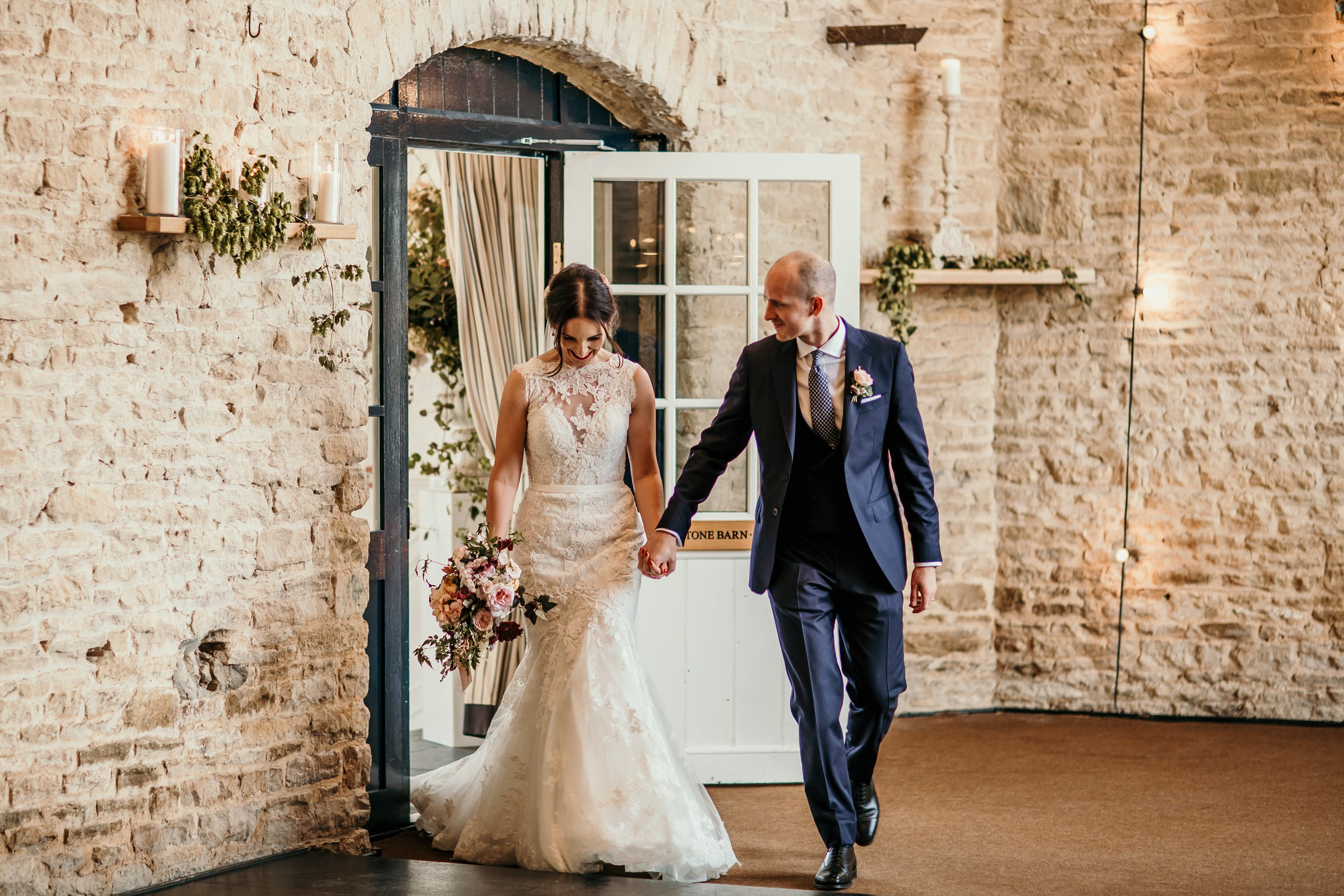 bride and groom enter the wedding barn at Merriscourt Barn Wedding venue by Cotswolds wedding photographer