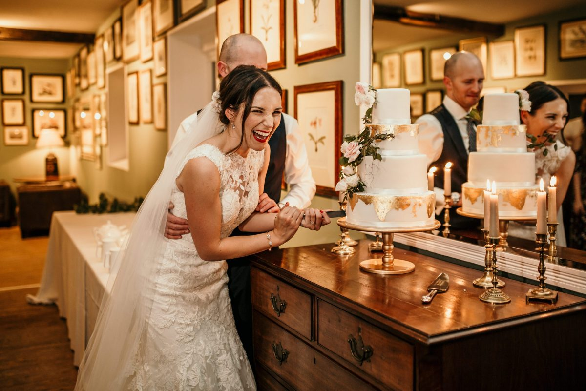 bride and groom cake cutting during the wedding reception at Merriscourt Barn Wedding venue by Cotswolds wedding photographer