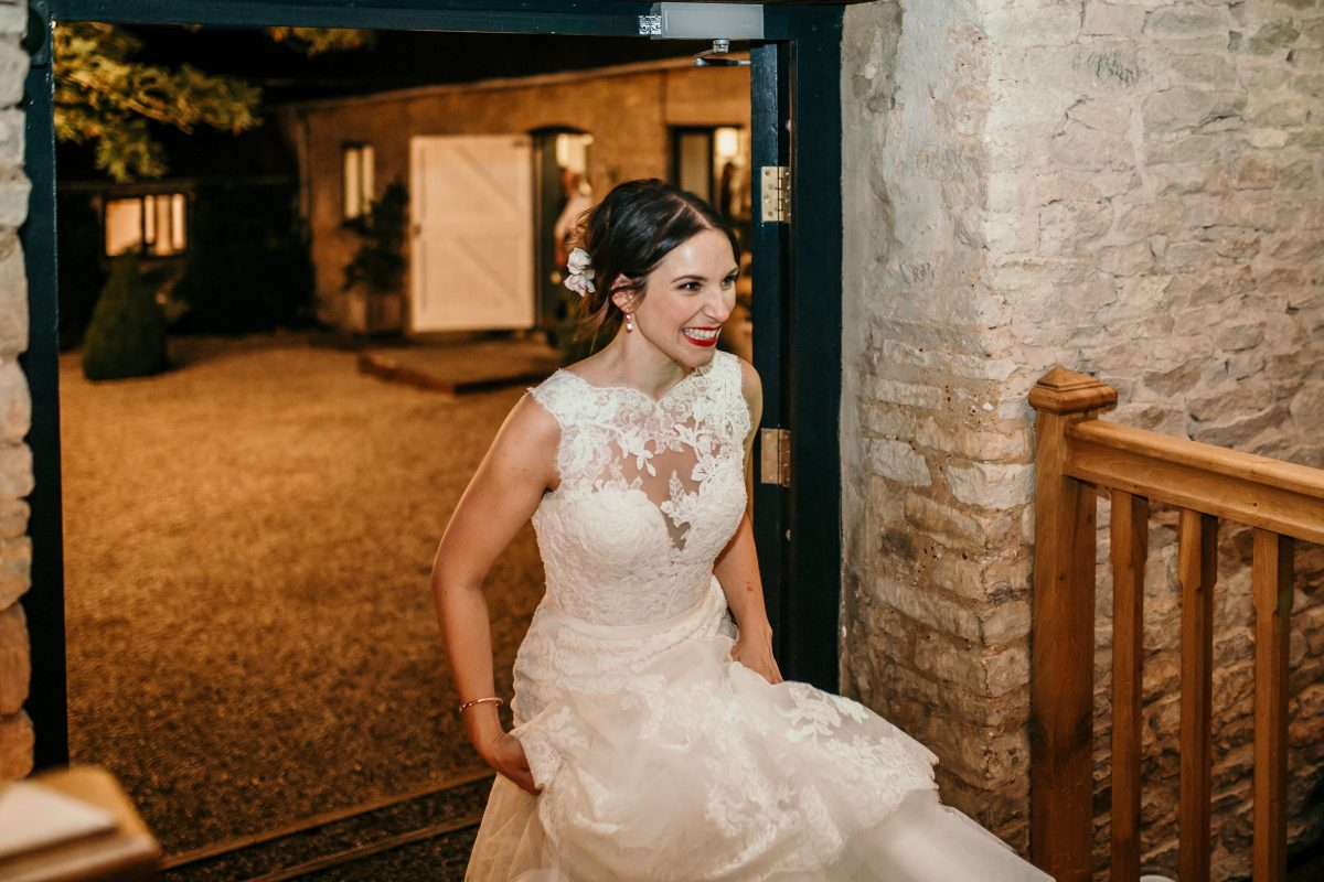 bride entering the barn at Merriscourt Barn Wedding venue by Cotswolds wedding photographer