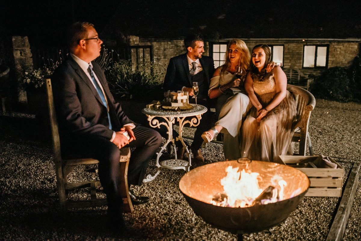 guests around the fire pit at Merriscourt Barn Wedding venue by Cotswolds wedding photographer