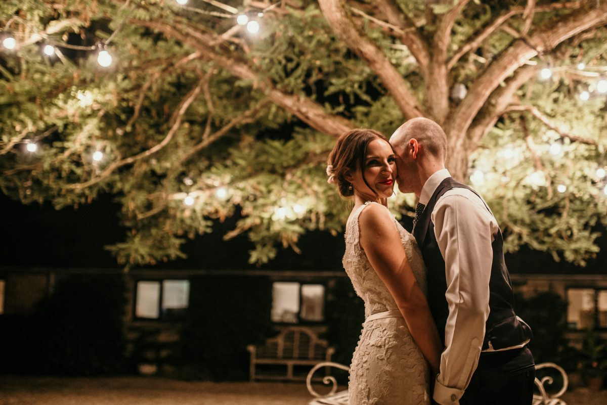 bride and groom kiss under fairy lights at merriscourt barn wedding venue cotswolds