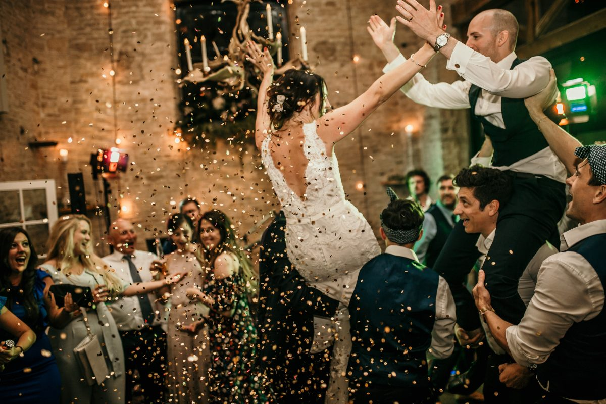 bride and groom on guests shoulders and glitter in the air during the wedding party at Merriscourt Barn Wedding venue by Cotswolds wedding photographer