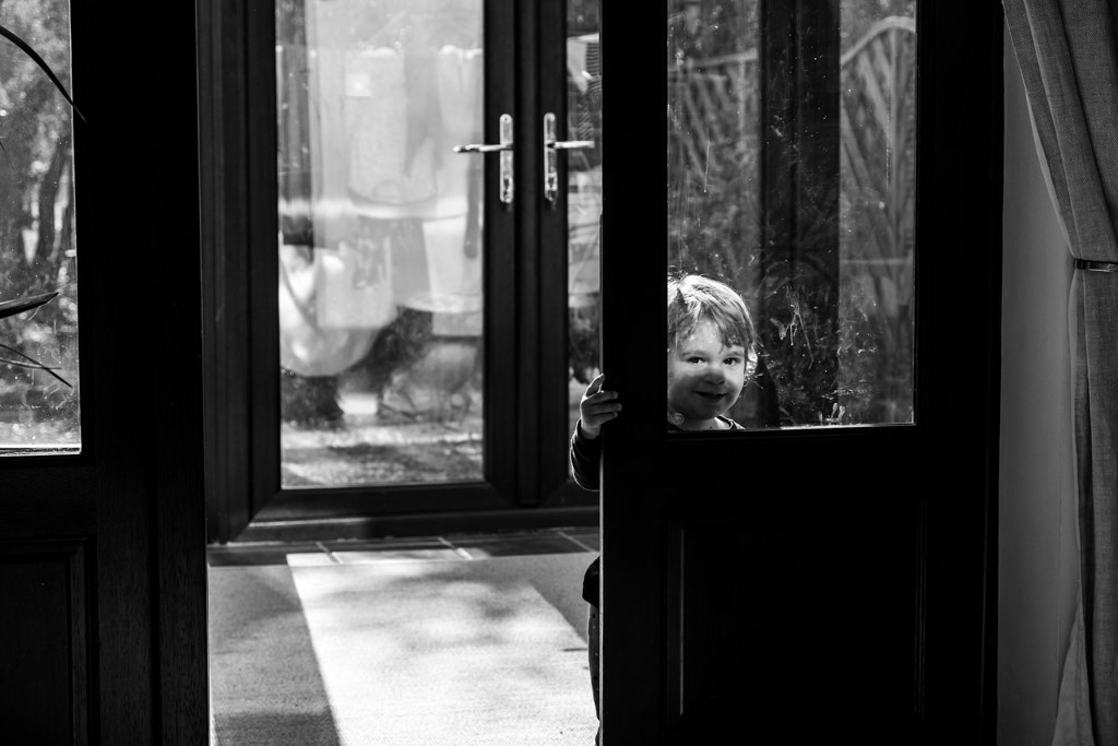 boy looking through door window in the conservatory