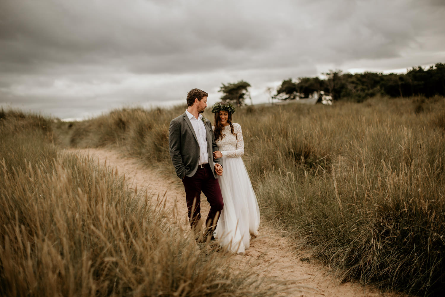 bride wearing an ethical wedding dress walking on the beach with her groom