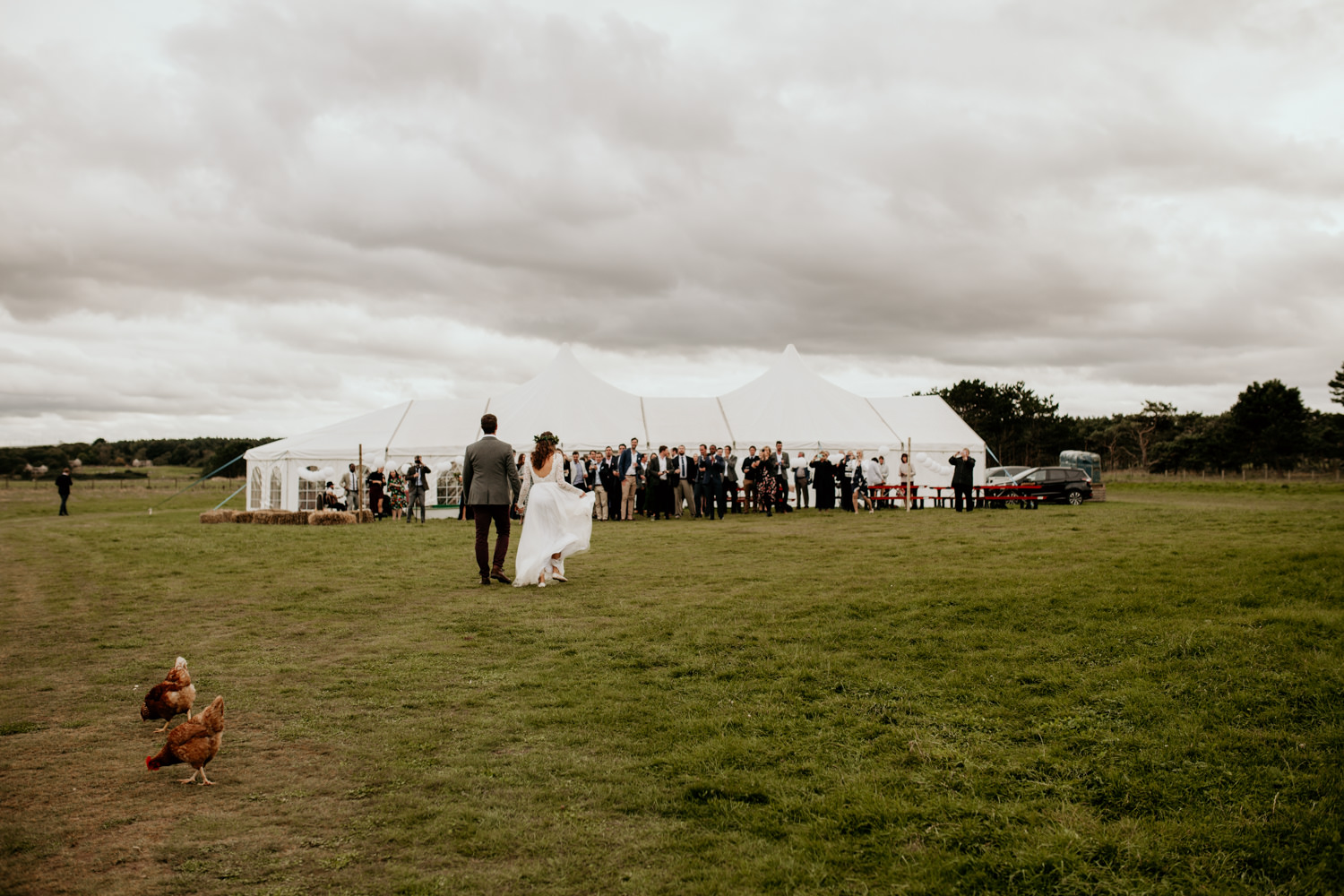 bride and groom walking towards the marquee at Harvest Moon Holidays Scotland