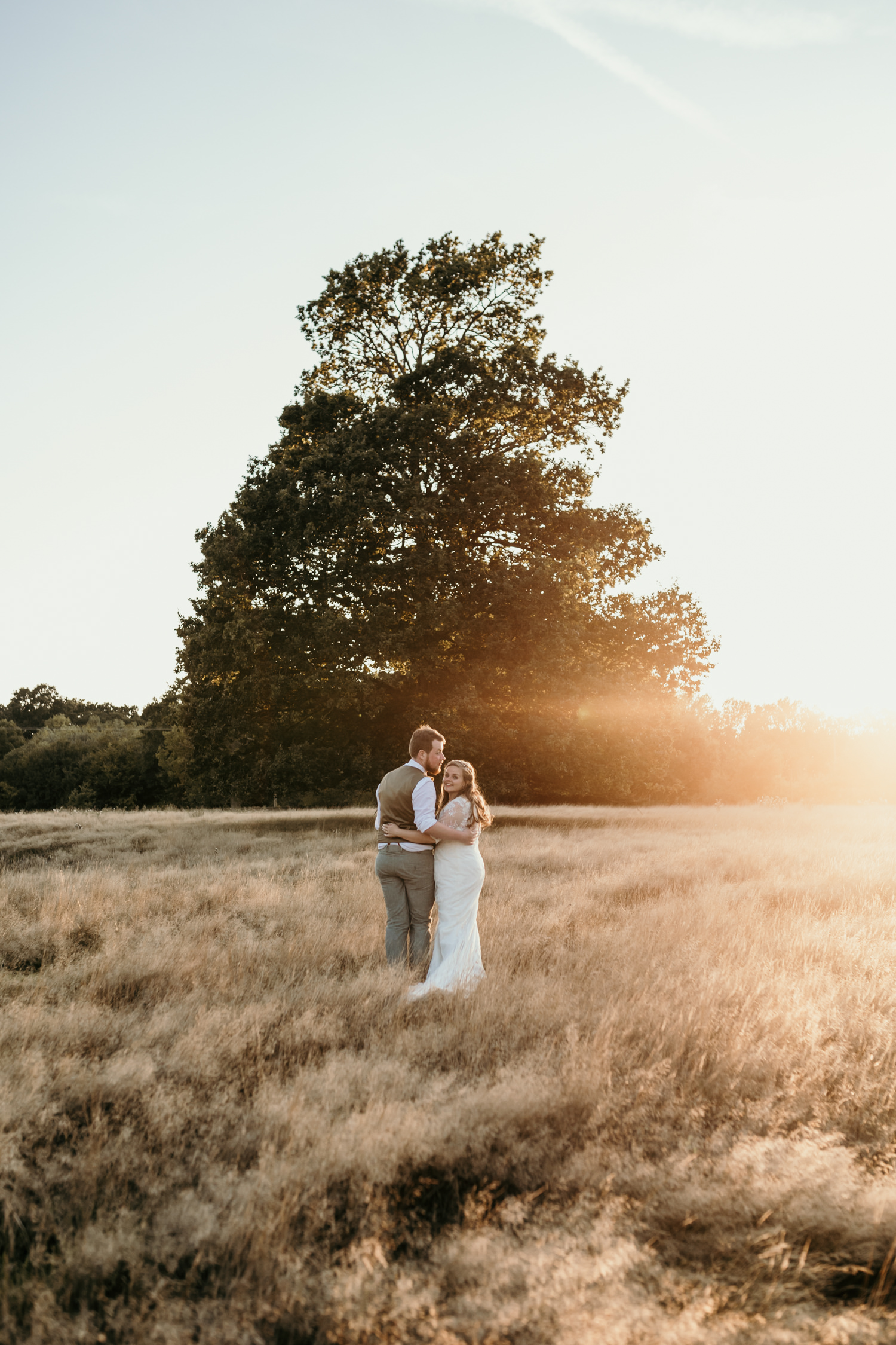 Bride and groom walking on the field during Sunset at The Cherry Barn