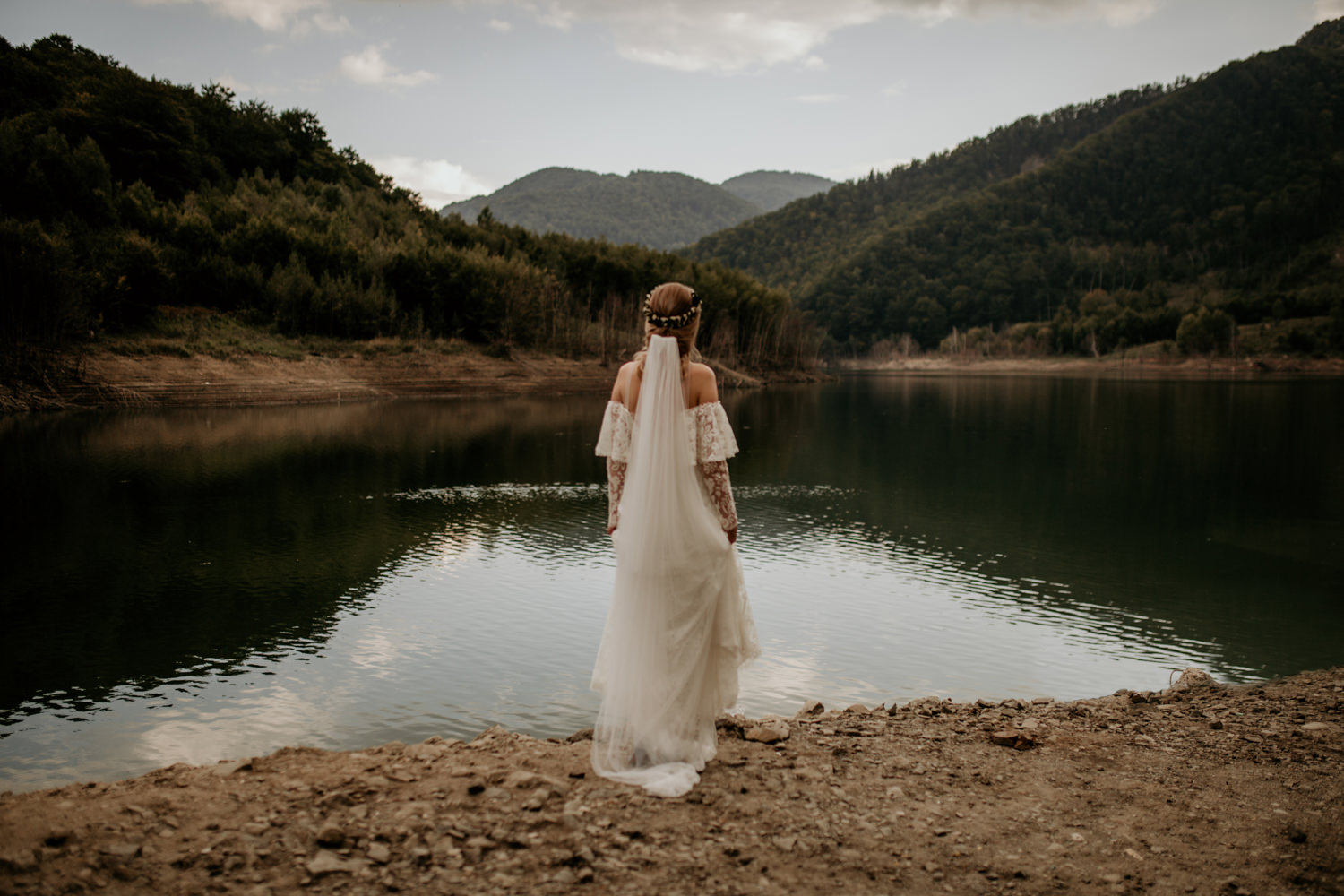 bride on the shore of a lake in the Carpathians mountains in Transylvania
