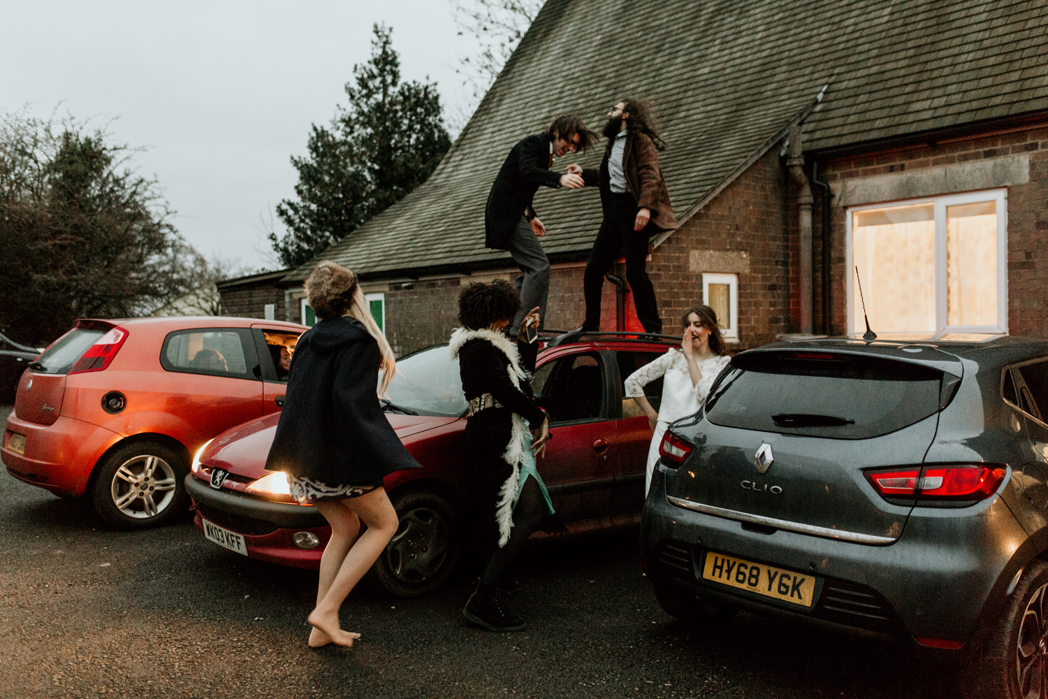 friends dancing on car after the wedding ceremony in the Cotswolds