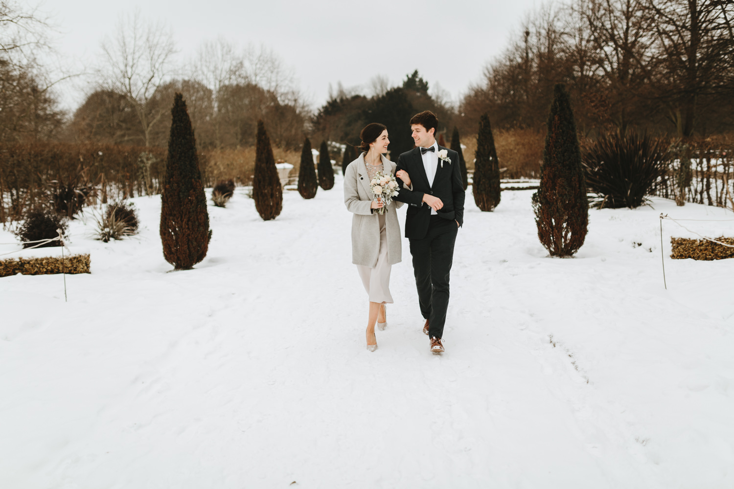 just married couple walking in the park on a snowy day after their civil marriage and Islington Town Hall