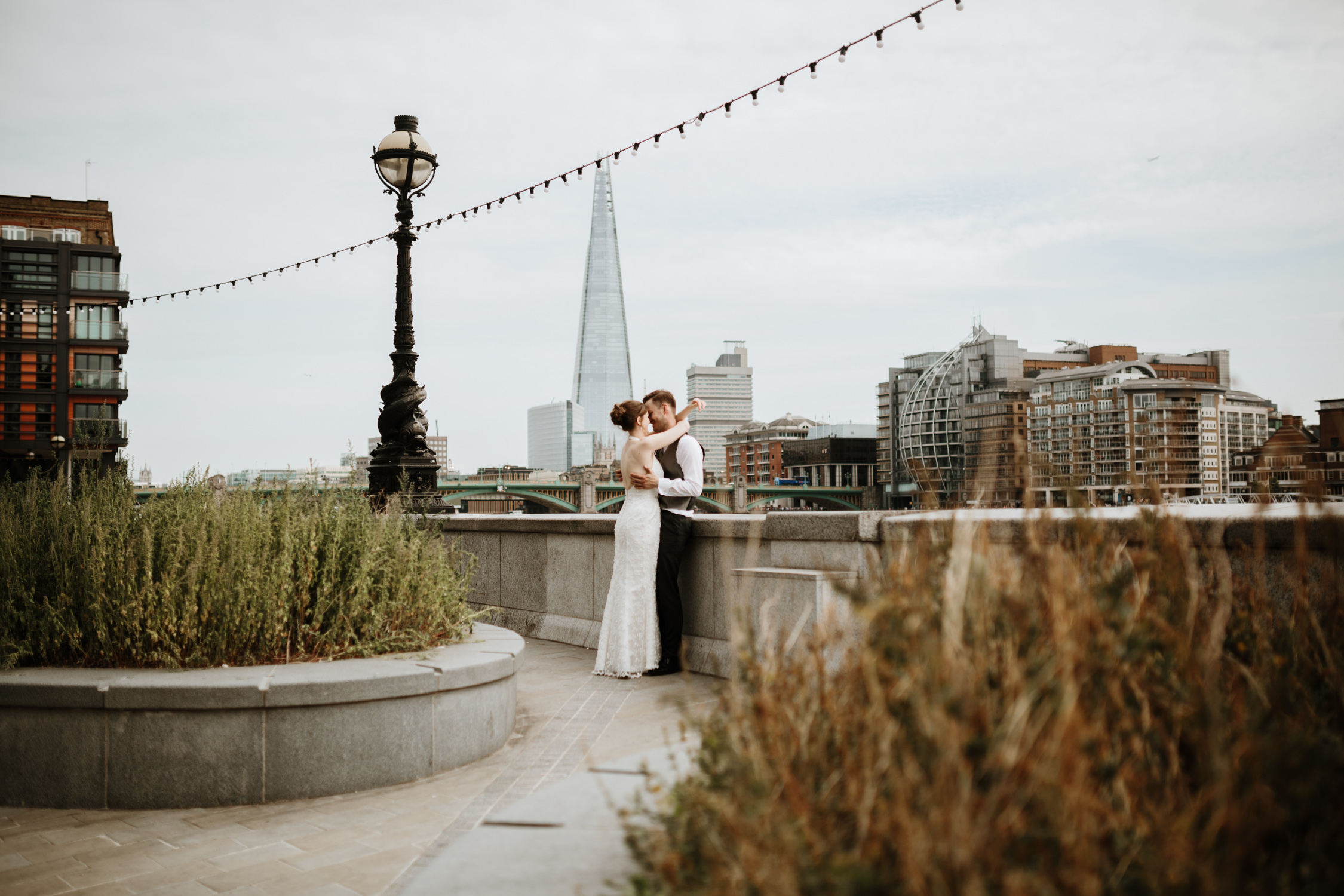 bride and groom kissing on a bridge in London after their elopement