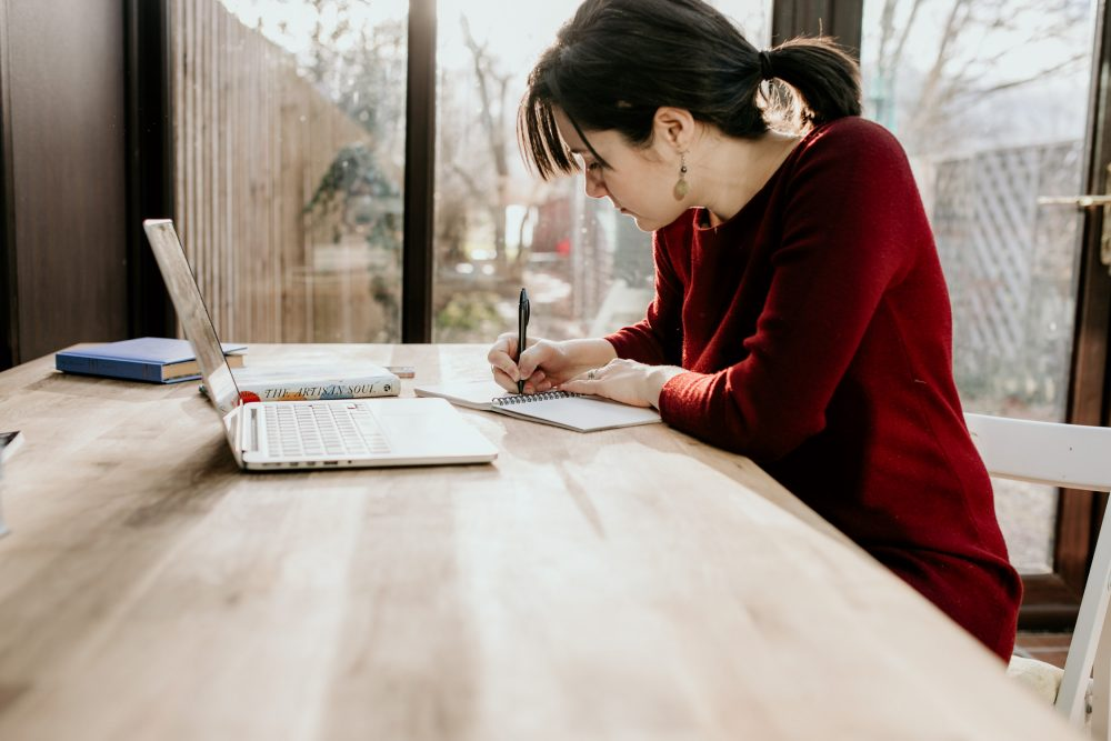 girl sitting at desk writing on a notebook how to plan a simple wedding