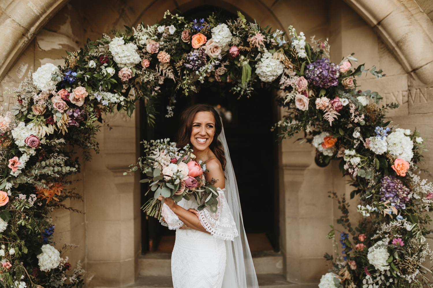 boho bride wearing a grace loves lace wedding dress and holding a bohemian wedding bouquet in front of a flower arch
