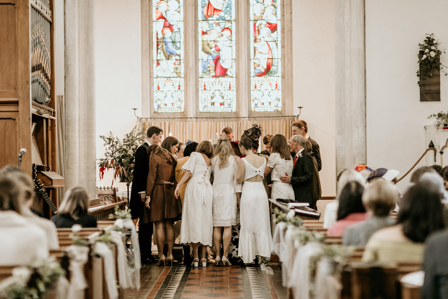 bridesmaids and friends praying for the bride and groom during their church wedding ceremony Stroud