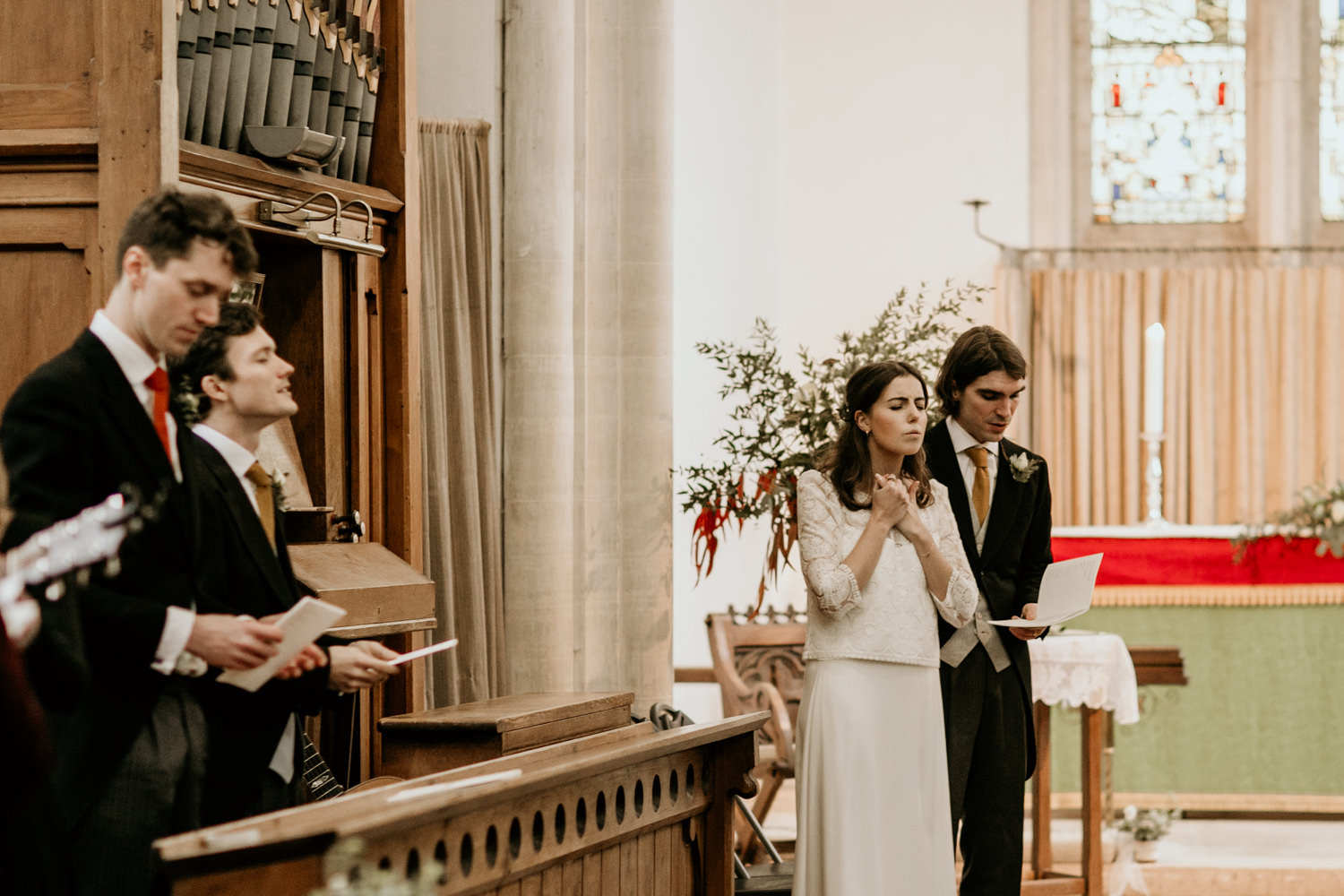 bride and groom singing during their church wedding ceremony Stroud Cotswolds