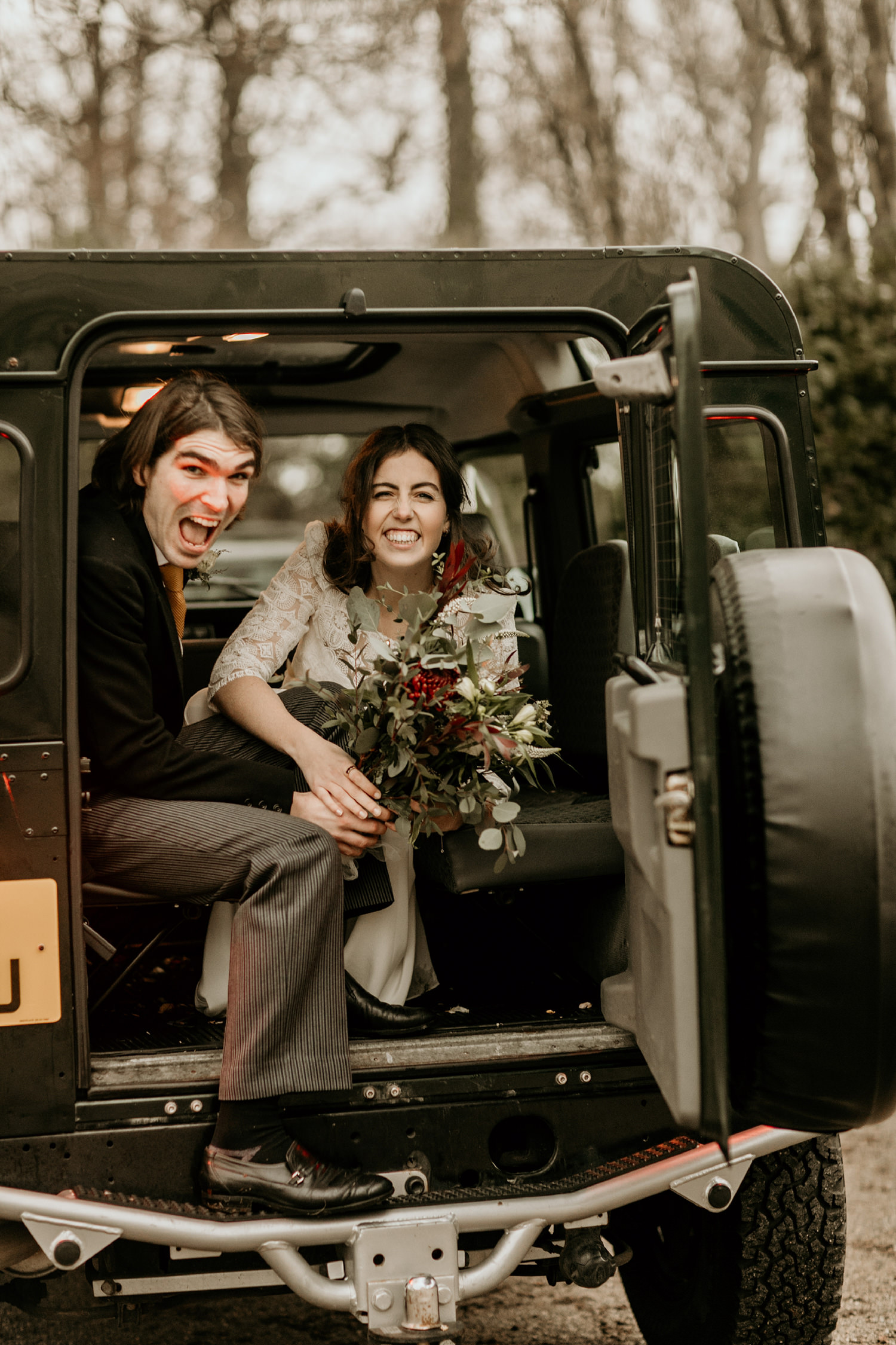 bride and groom at the back of a discovery car, after their wedding portraits in Stroud