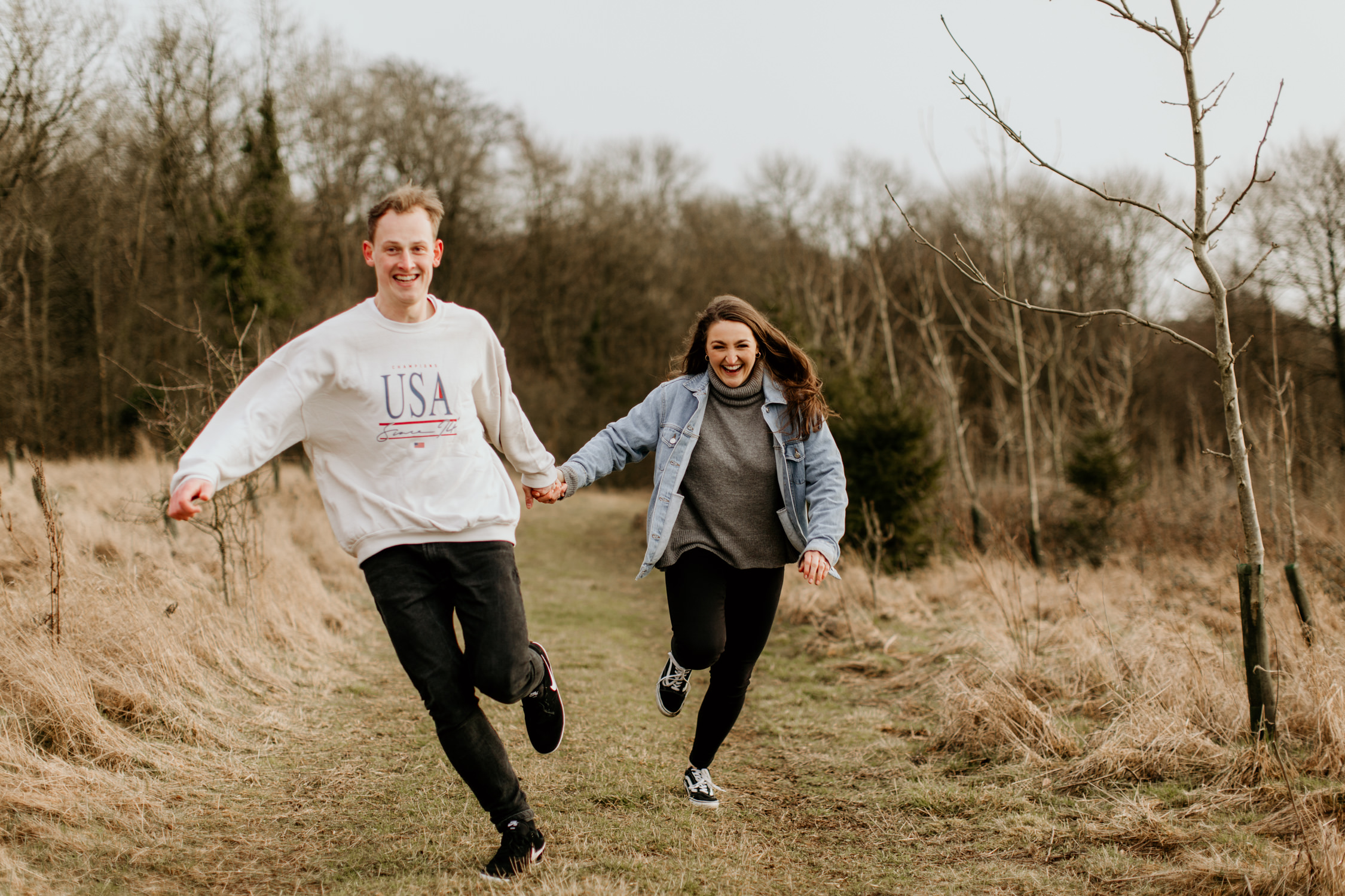 fun shot of couple running during their engagement shoot in the Cotswolds countryside