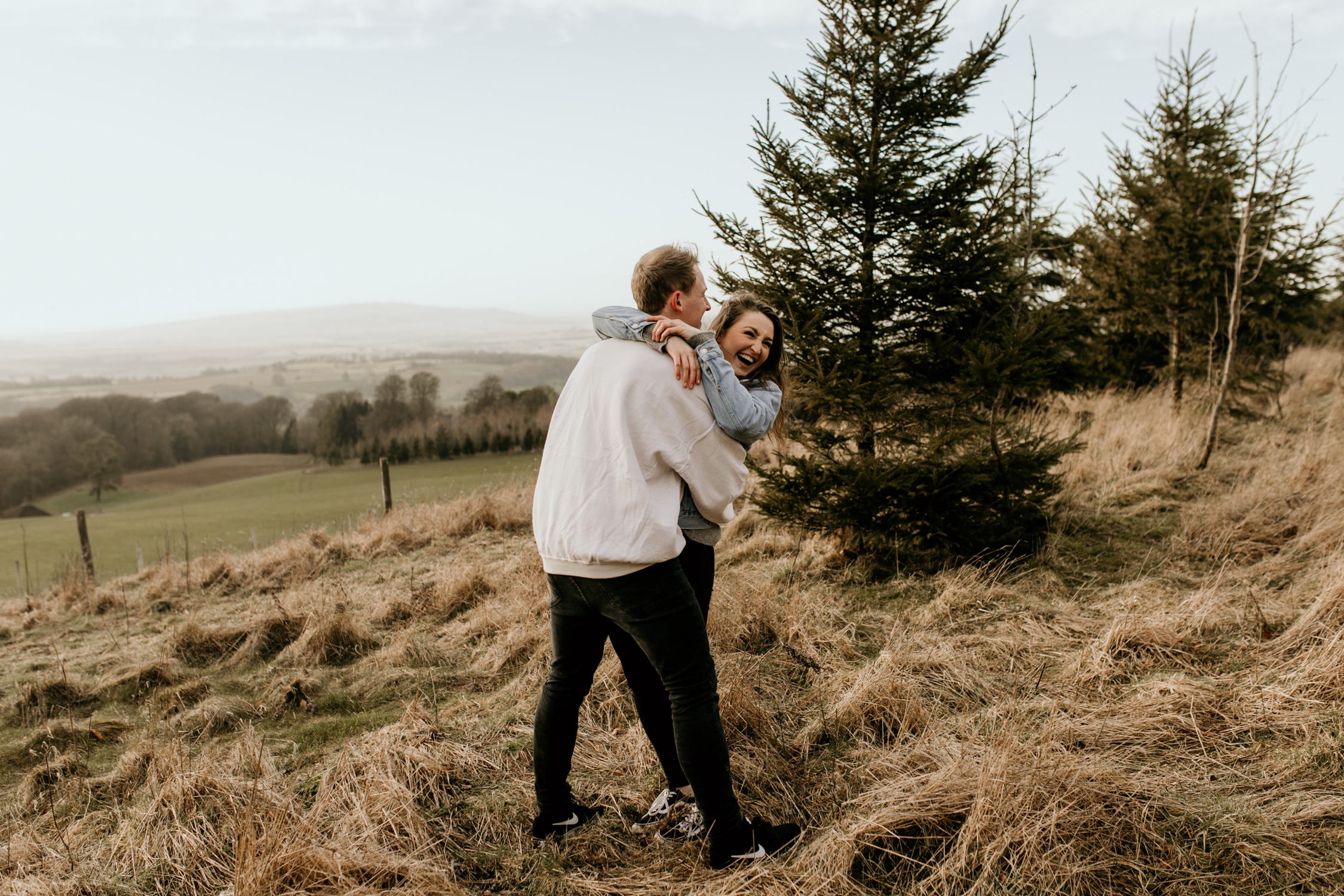 couple having fun during their engagement shoot in the Cotswolds countryside