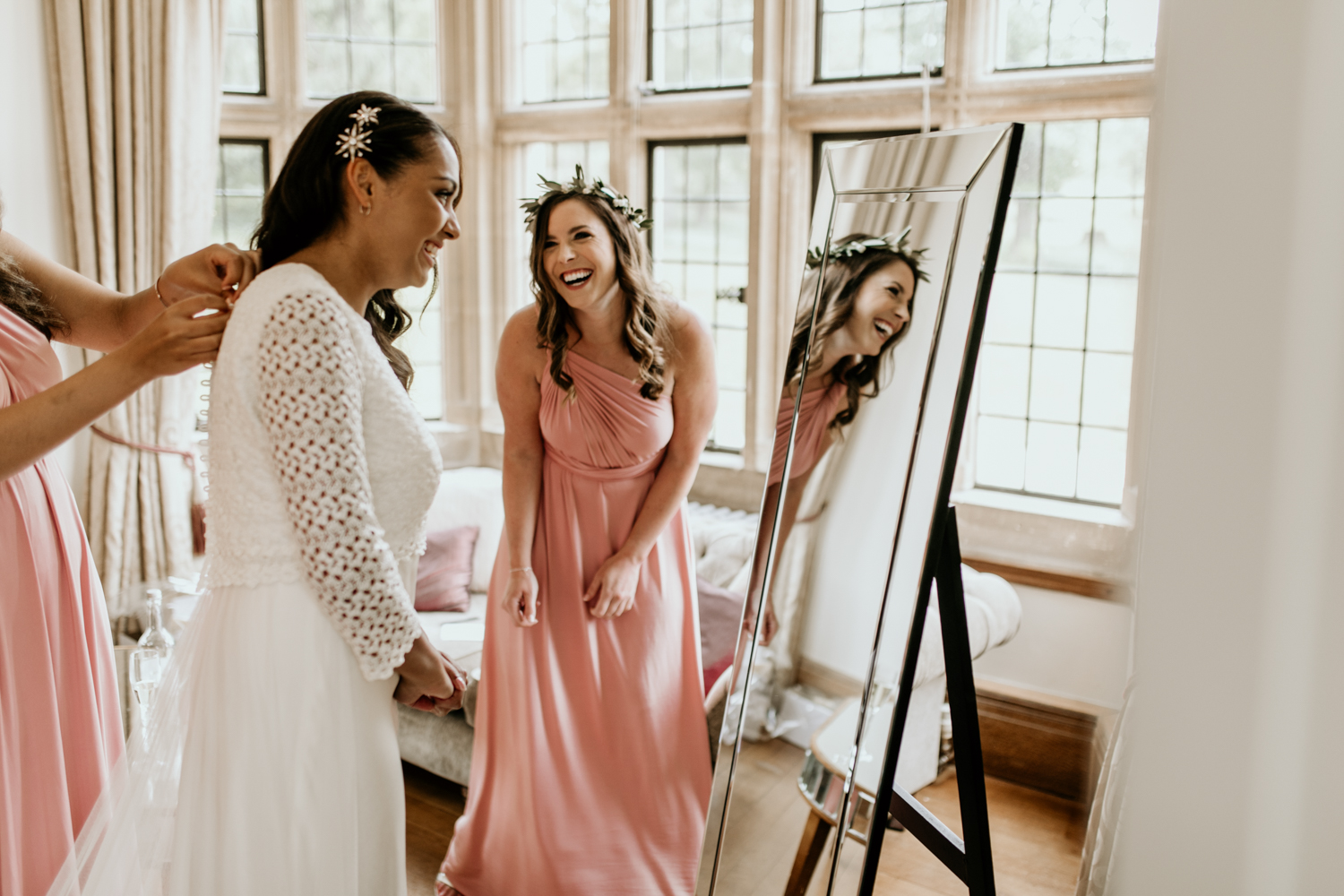 bridesmaids and bride in front of mirror before the outdoor wedding ceremony at Coombe Lodge Blagdon wedding venue