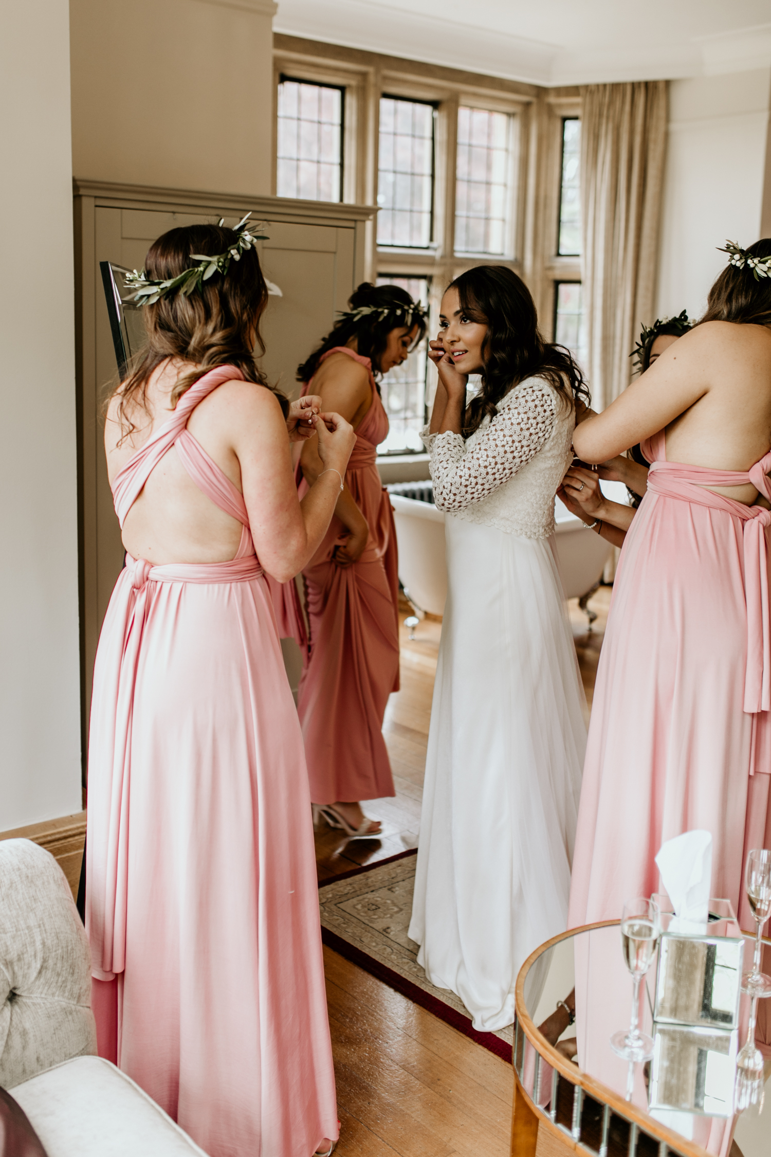 bride getting jewellery on before the outdoor wedding ceremony at Coombe Lodge Blagdon wedding venue