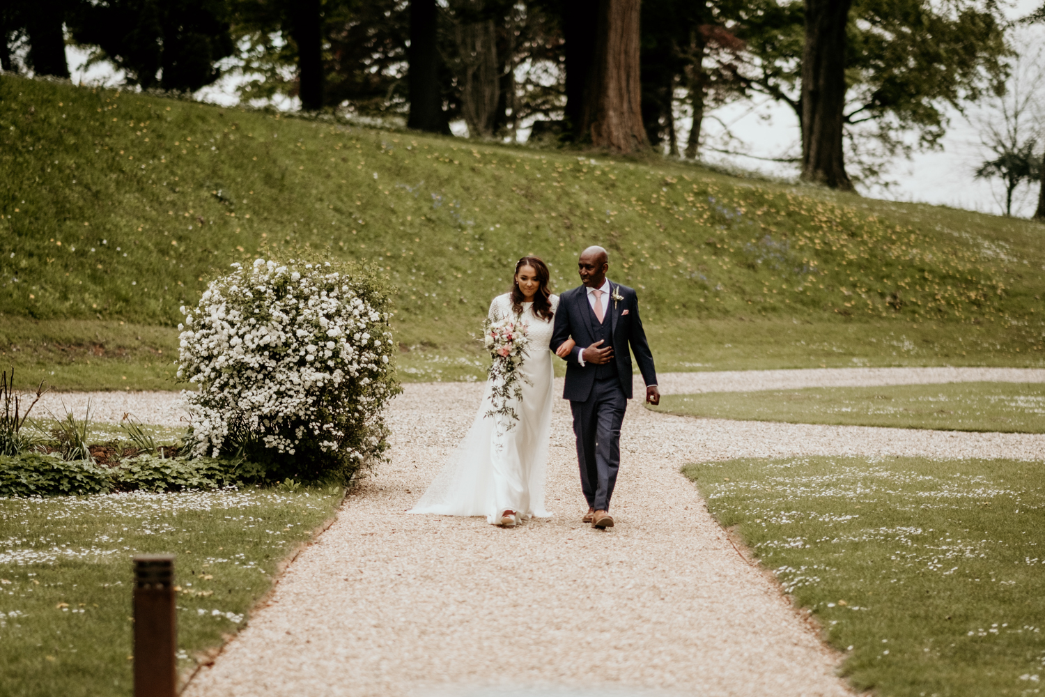 bride and dad walking down the aisle for here outdoors wedding ceremony