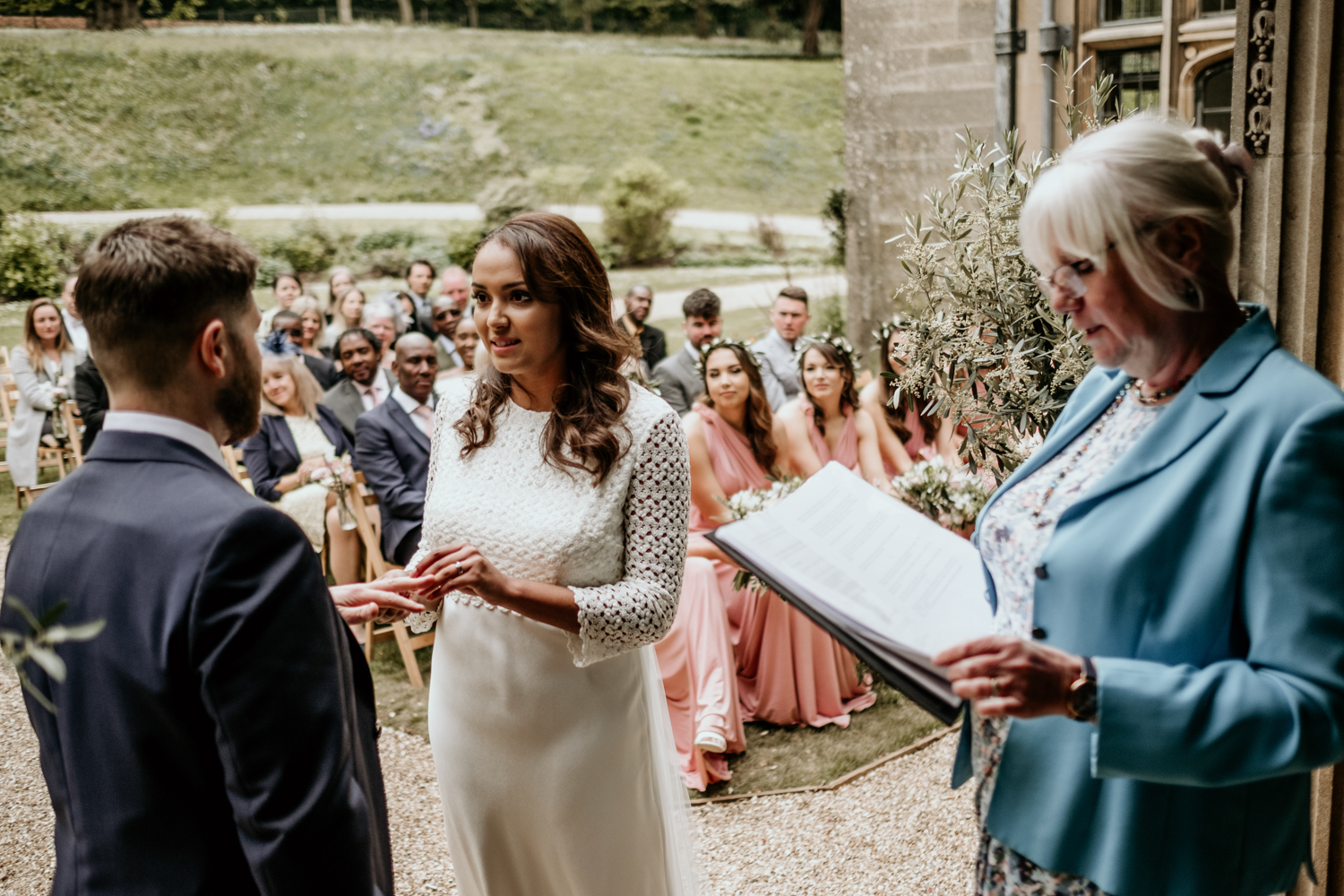 bride and groom exchange rings at Coombe Lodge Blagdon wedding venue