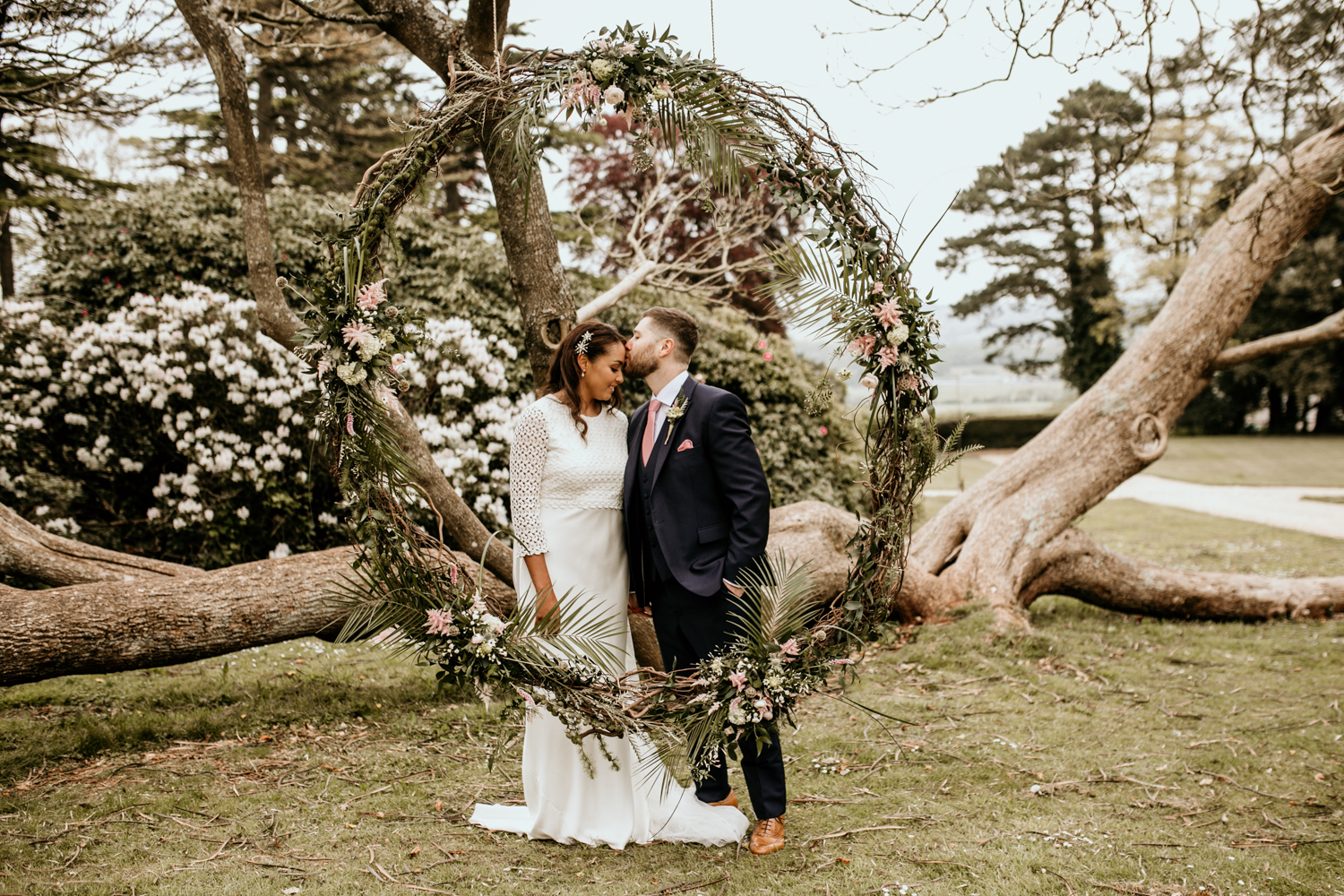 bride and groom kiss in front of a big flower circle at Coombe Lodge Blagdon wedding venue