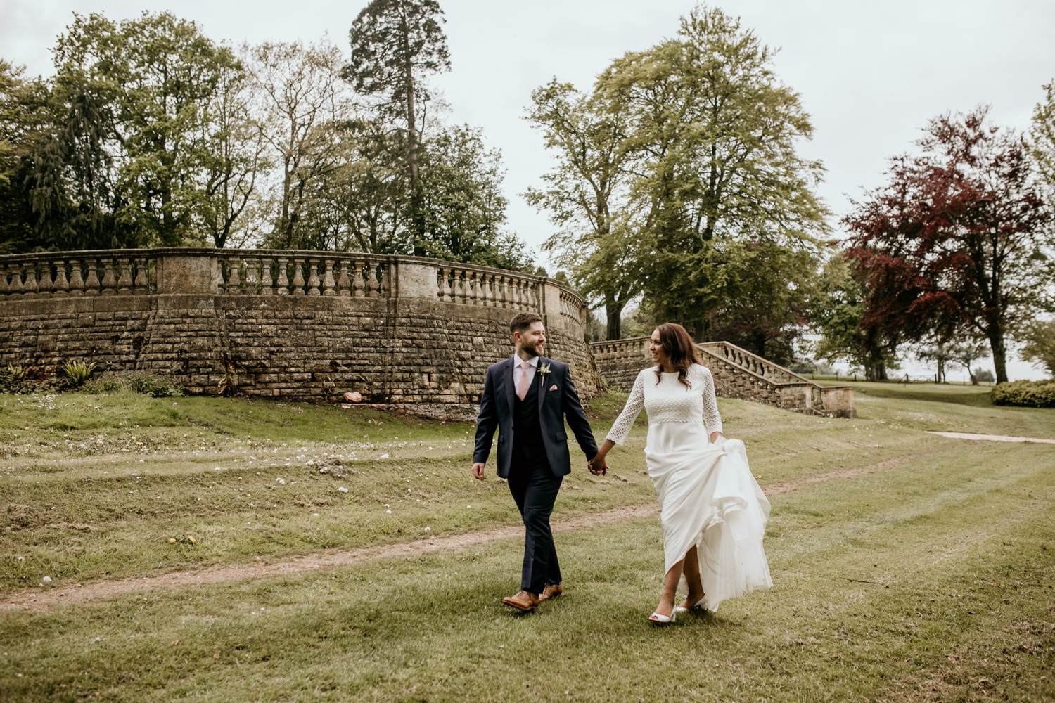 bride and groom walking during their wedding portraits at Coombe Lodge Blagdon wedding venue
