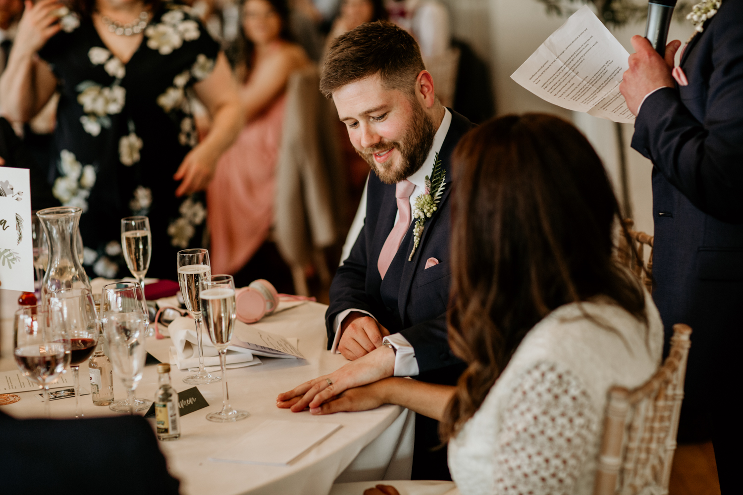 bride and groom hold hands during speech at Coombe Lodge Blagdon wedding venue