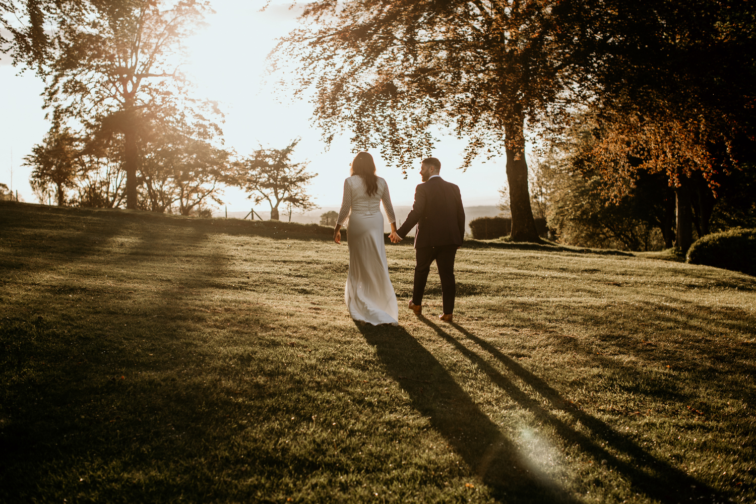 bride and groom walking during sunset at Coombe Lodge Blagdon wedding