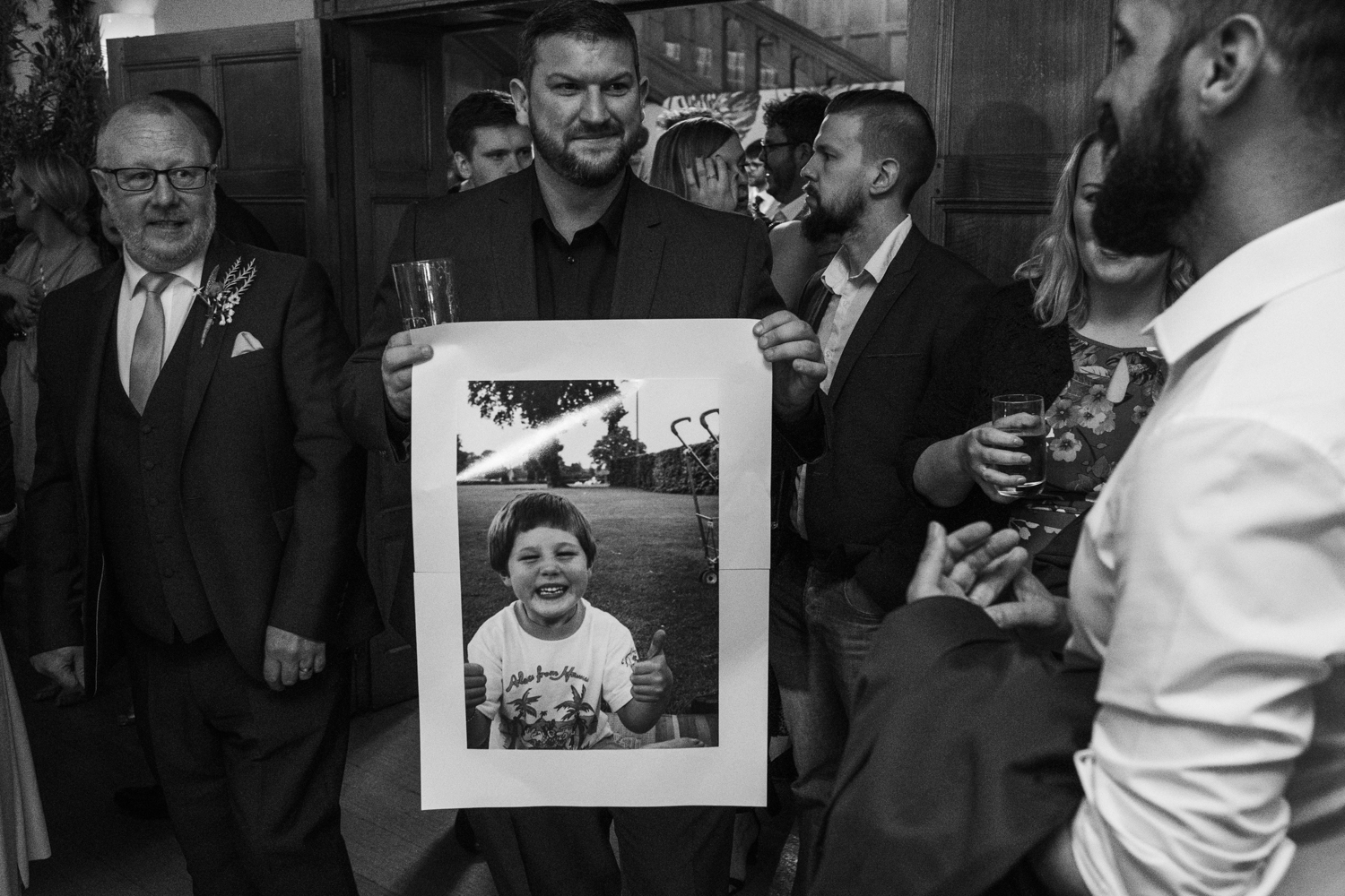 guest walking with a childhood picture of the groom during the wedding reception
